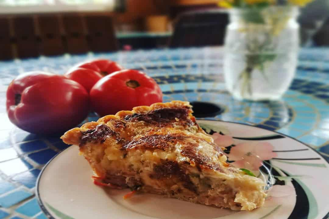 Slice of quiche on blue table with tomatoes